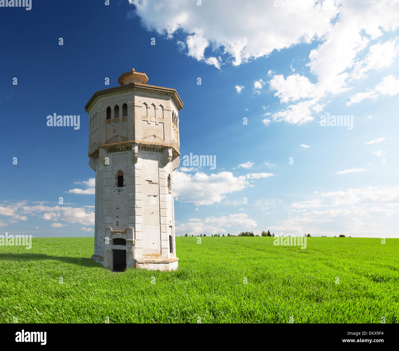 green field and ancient stone tower - Stock Image