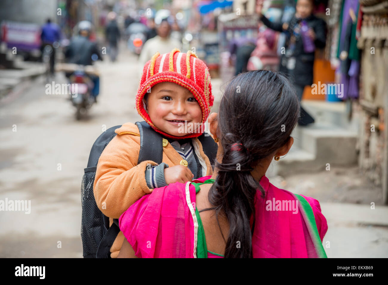 A young nepali child in his mother's arms is looking at the camera, in Kathmandu's streets, Nepal - Stock Image