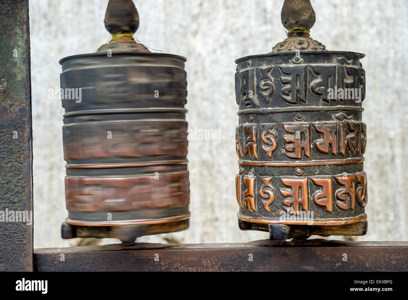 Two prayer wheels at Swayambhunath Monkey temple in Kathmandu, Nepal. One is still, the other one is turning (blur - Stock Image
