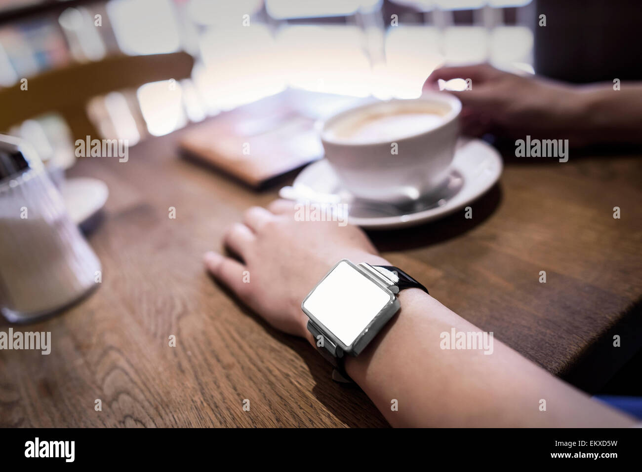 In coffee bar a woman using her smartwatch. - Stock Image