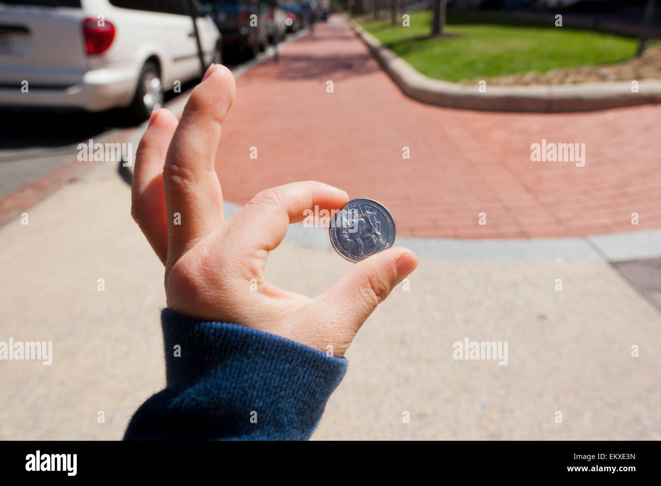 Boy, age 6, holding a coin found on sidewalk - USA - Stock Image