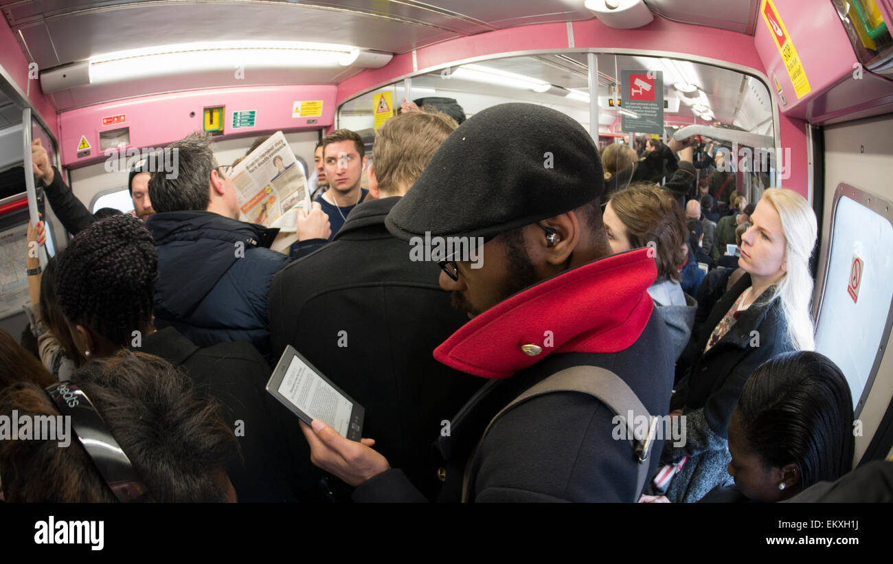 Packed overcrowded London commuters in overground train squeezed in during rush hour, with male reading kindle - Stock Image
