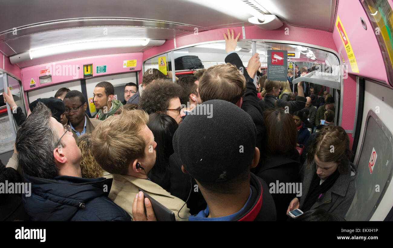 Packed overcrowded London commuters in overground train squeezed in during rush hour - Stock Image