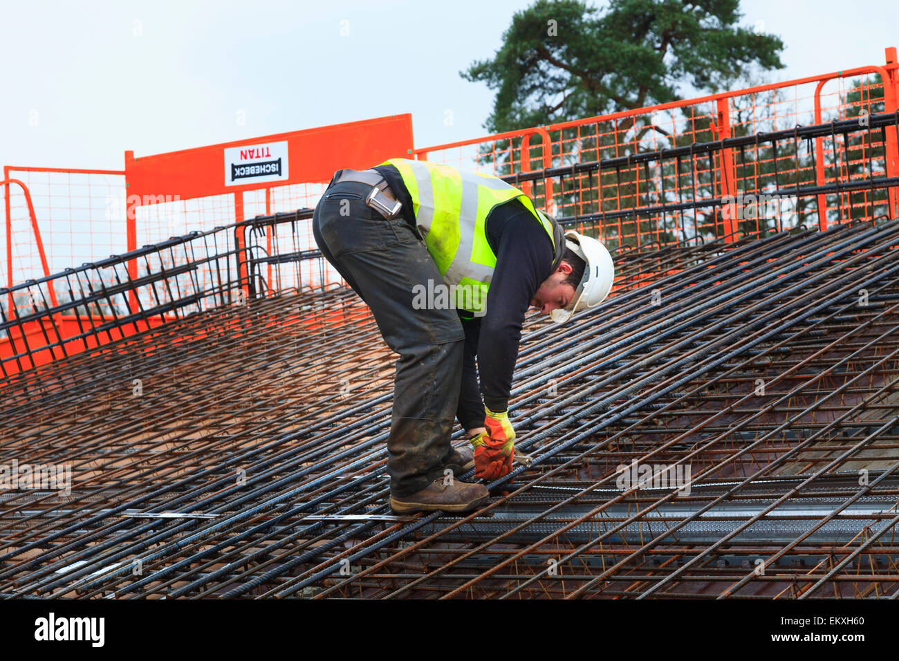 Construction worker tying up reinforcing bars prior to pouring of concrete on a commercial building roof. - Stock Image