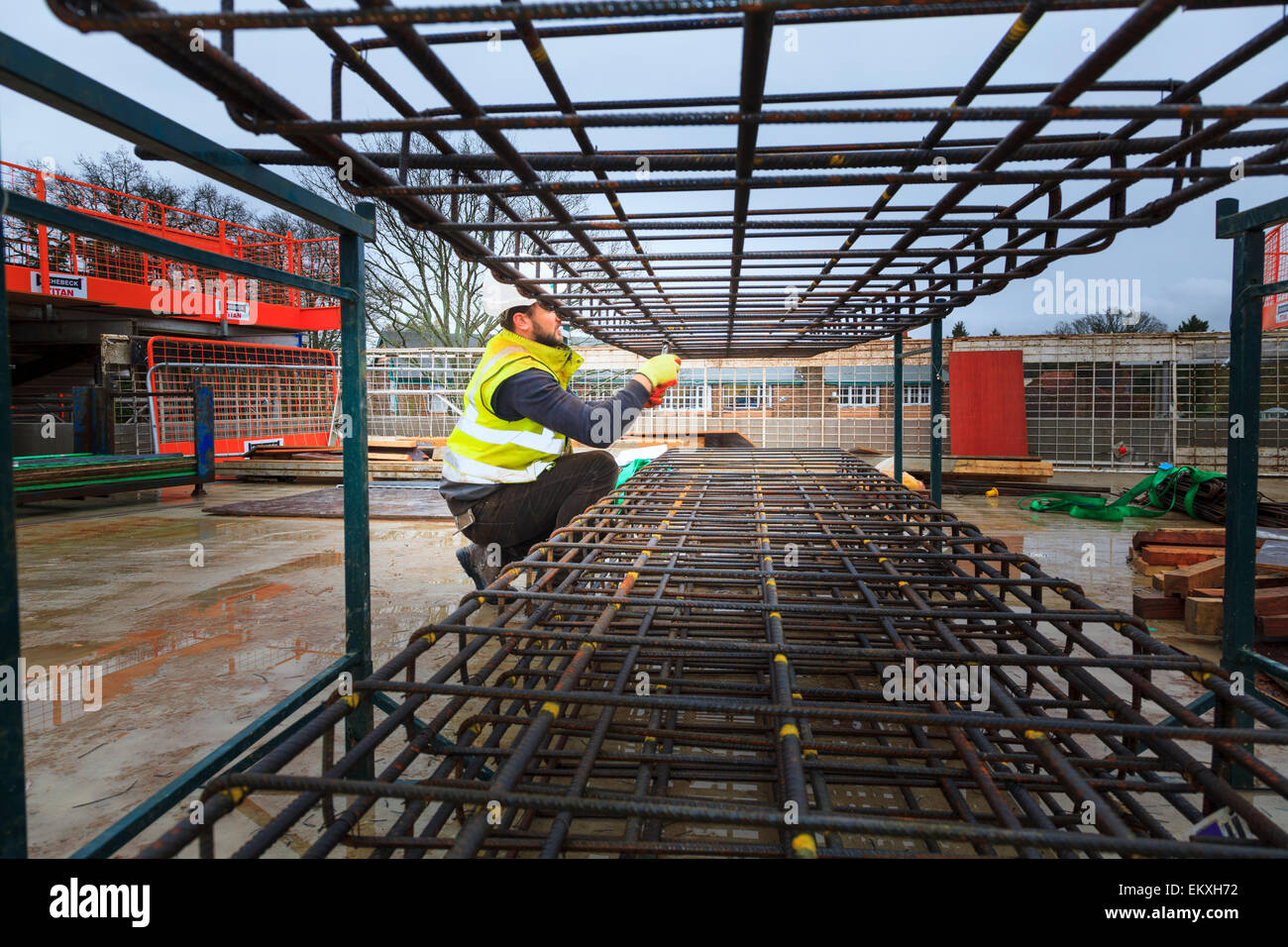 Construction worker forming concrete reinforcing bars - Stock Image
