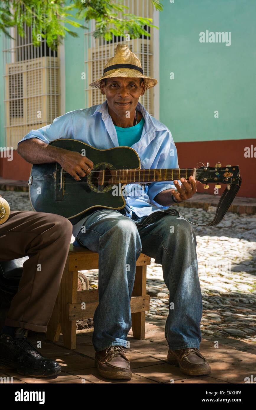 Cuba Trinidad Plaza Mayor area musical group band busk buskers musicians play guitar shade tree by Iglesia de San - Stock Image