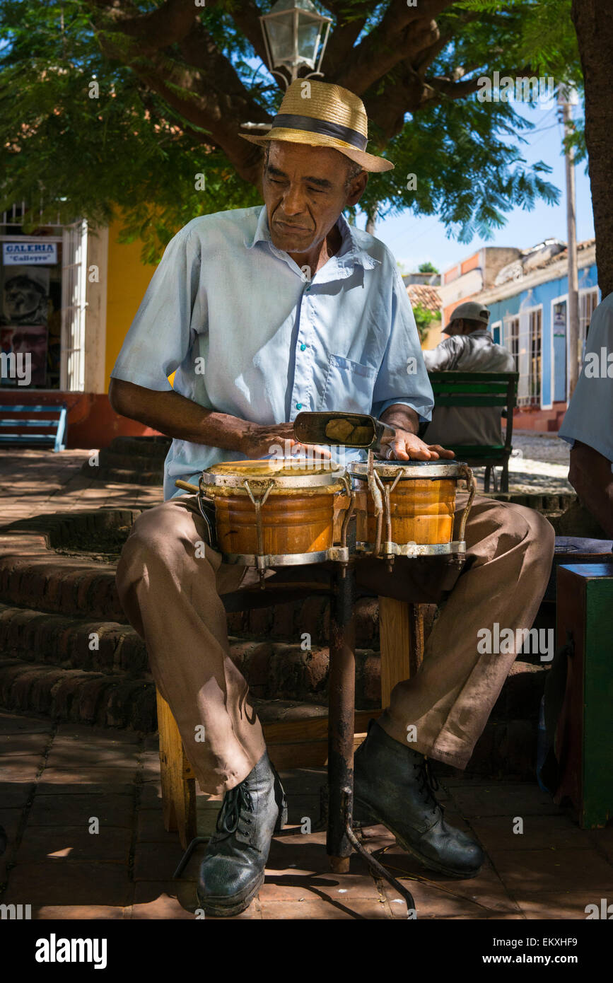 Cuba Trinidad Plaza Mayor area musical group band busk buskers musicians play bongo drums shade tree by Iglesia - Stock Image
