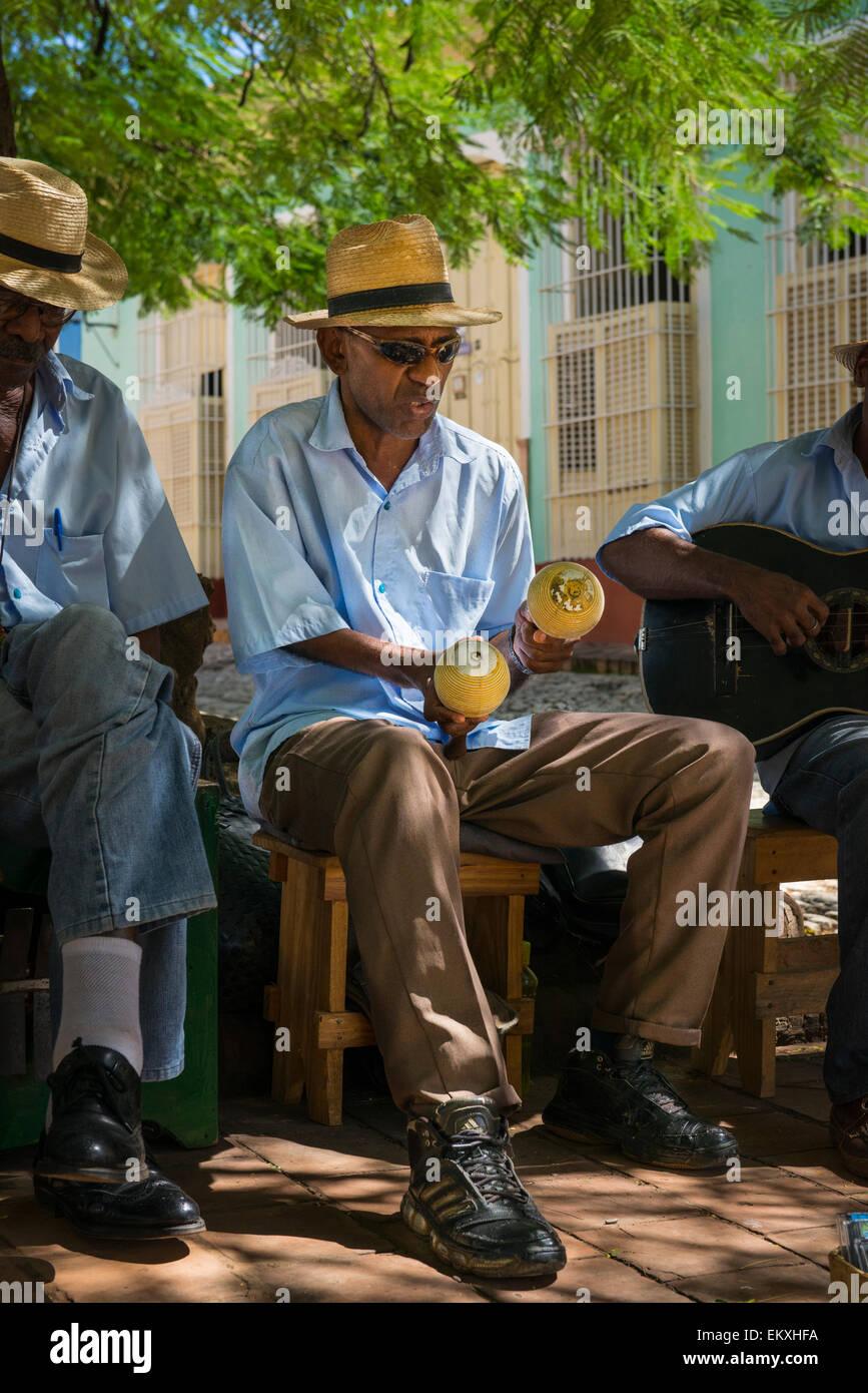 Cuba Trinidad Plaza Mayor area musical group band busk buskers musicians play maracas in shade tree by Iglesia de - Stock Image