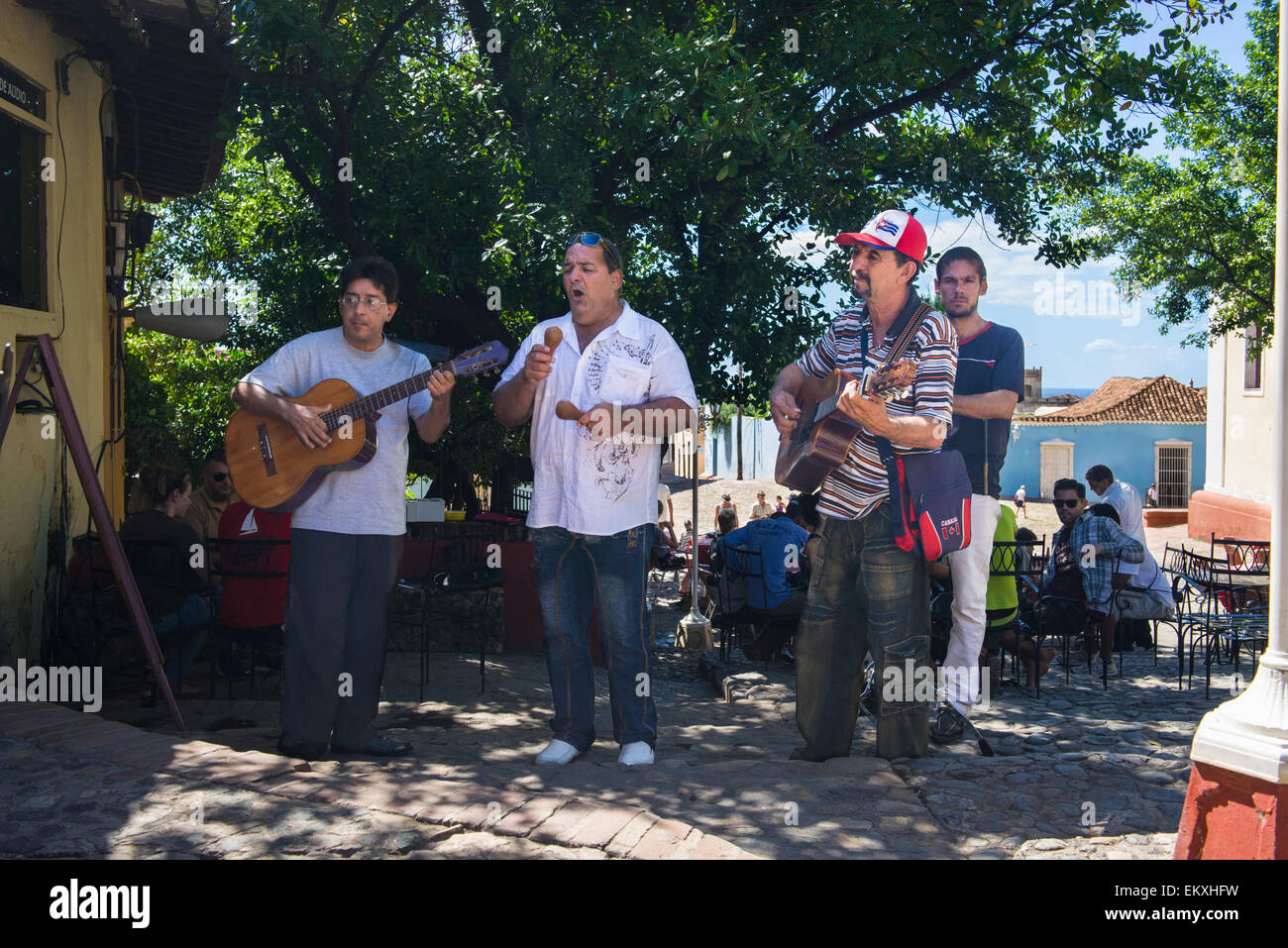 Cuba Trinidad Plaza Mayor area bar cafe musical group band busk buskers guitars singer outside by tree - Stock Image