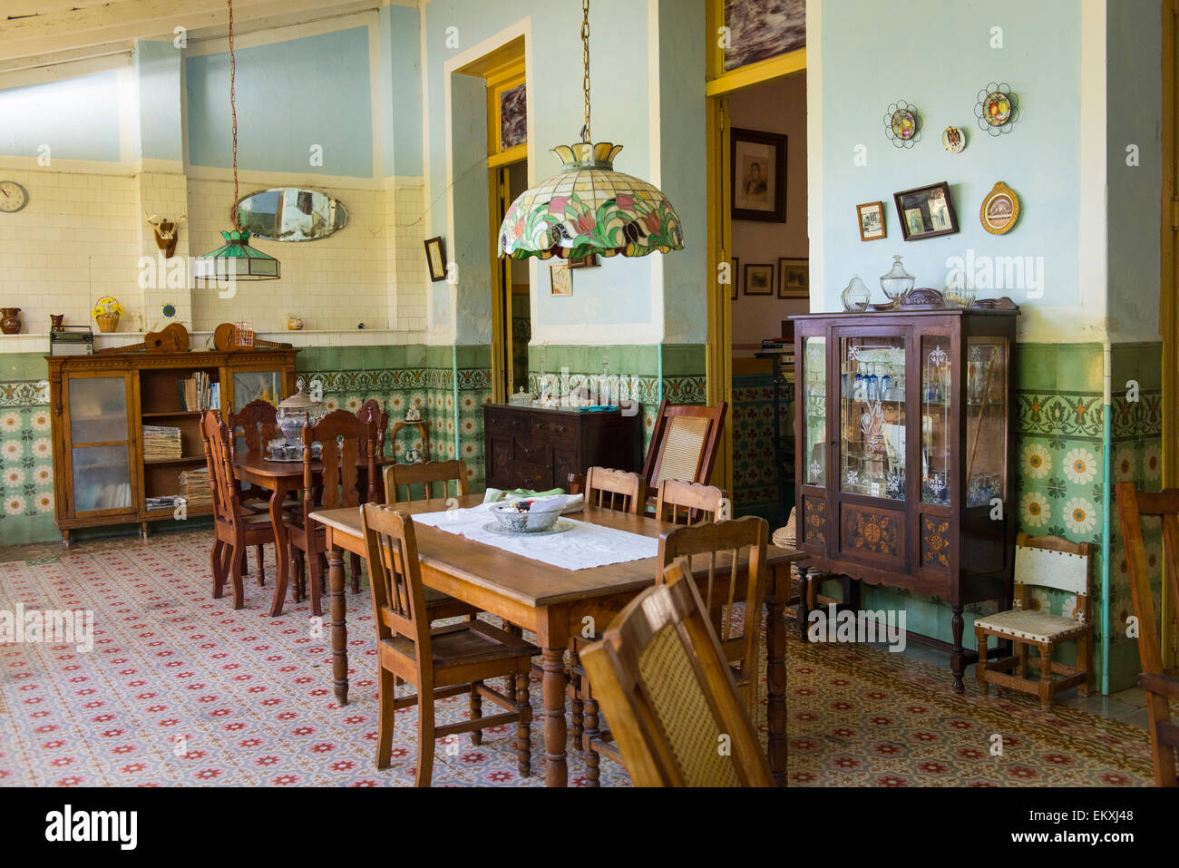 Cuba Trinidad typical Cuban home old antique furniture sideboard vitrine ornate walls & tiles lamp shades table - Stock Image
