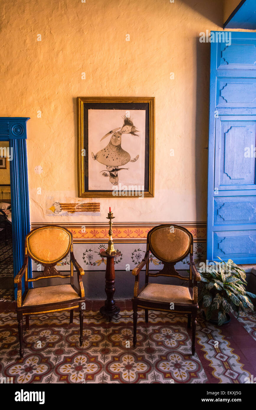 Cuba Trinidad typical Cuban home sitting room antique chairs candlestick  blue shutters painting ornate walls & tile tiles - Cuba Trinidad Typical Cuban Home Sitting Room Antique Chairs Stock
