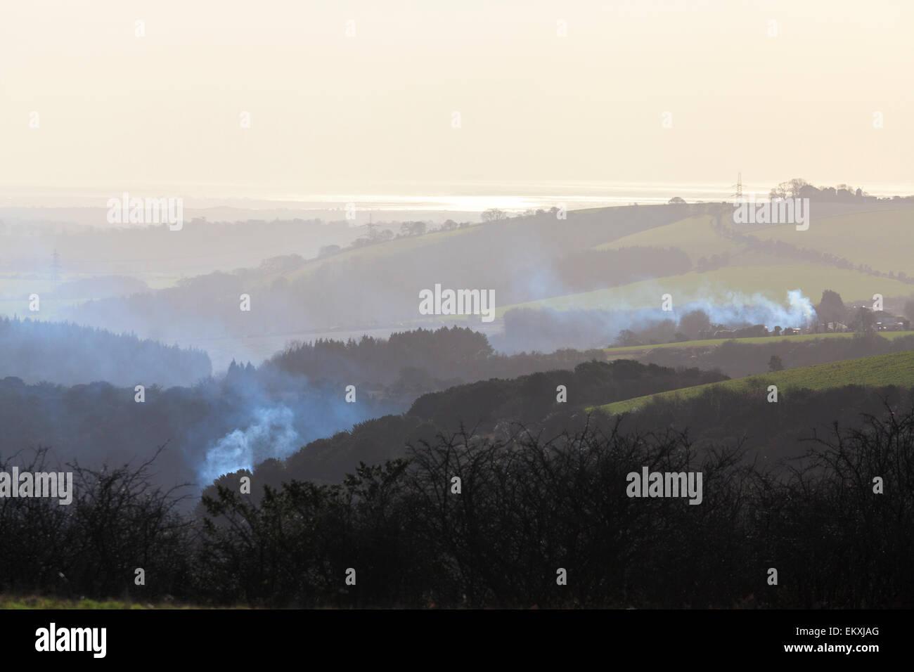 Smoke rising on hilly hazy landscape - Stock Image