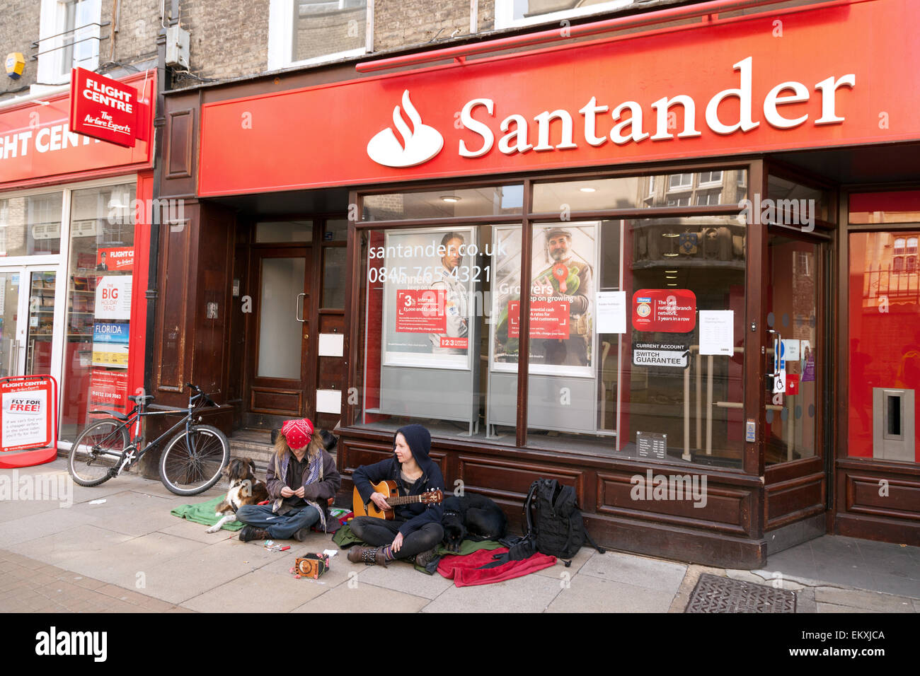 Buskers busking outside the Santander Bank, an example of the concept of rich and poor, Sidney Street, Cambridge - Stock Image