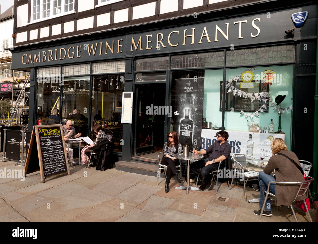 People sitting drinking outside Cambridge Wine Merchants on a sunny day, Cambridge England UK - Stock Image