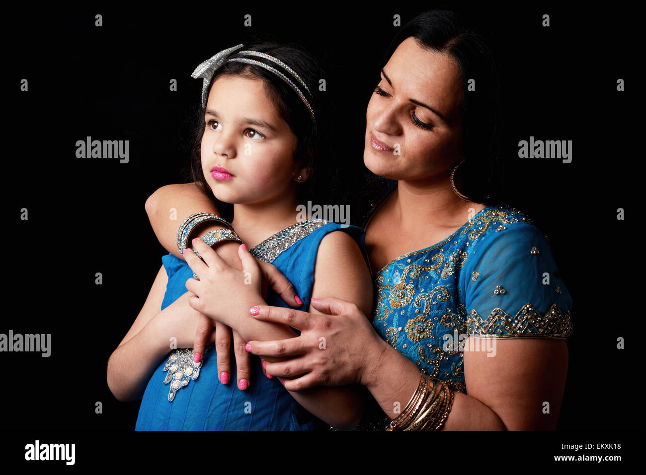 A mother and her daughter in a studio against  a black background - Stock Image