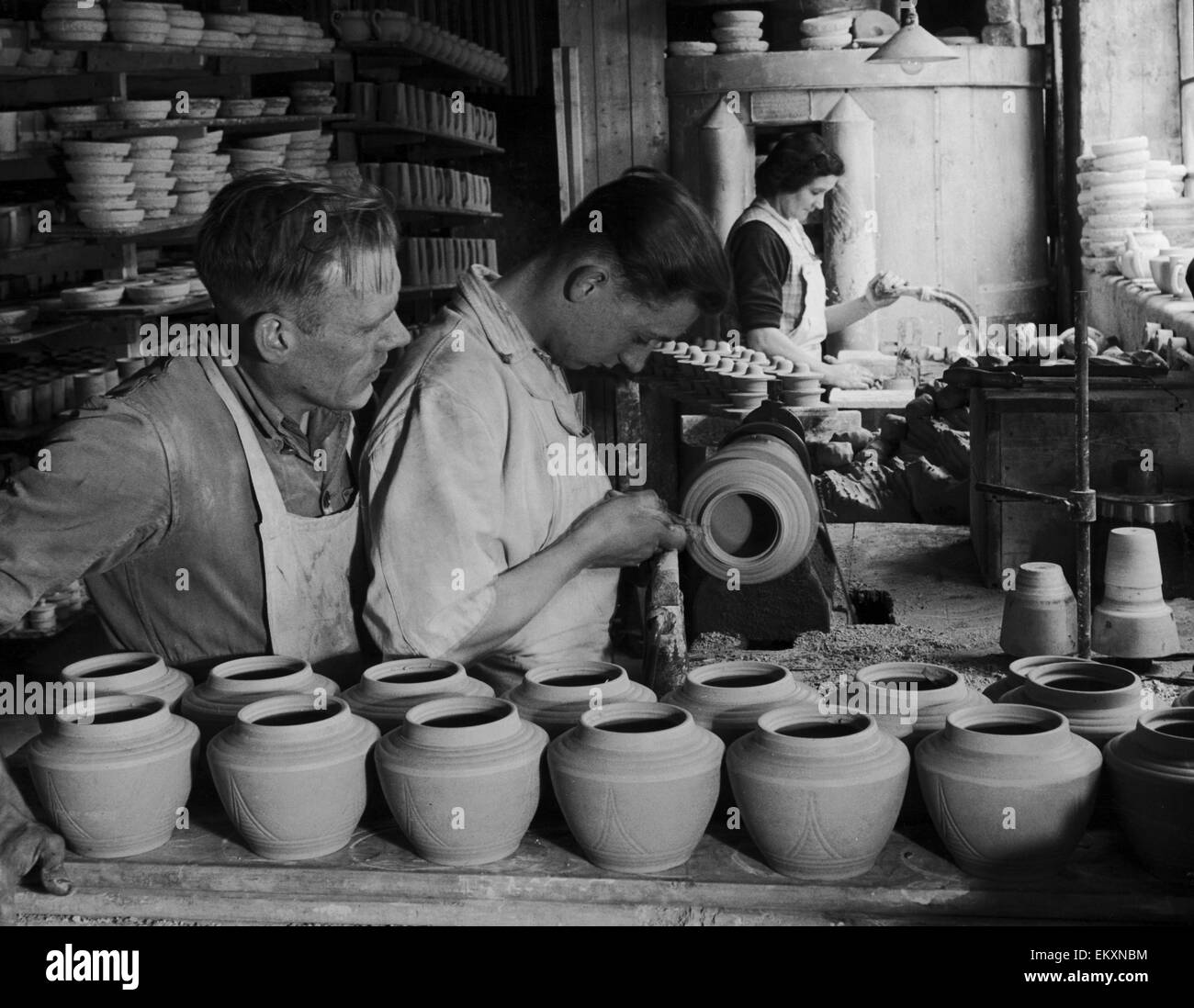 Seventeen year old Len Mills, apprenticed turner of teapots and teapot lids at a Stoke On Trent pottery, produces - Stock Image