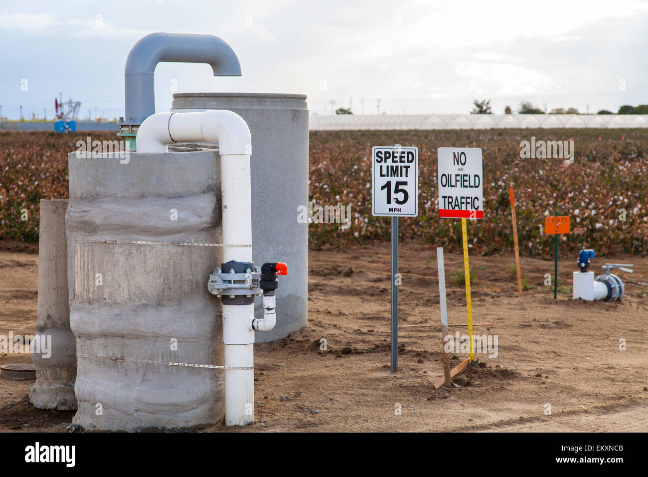 No oilfield traffic sign next to groundwater well with oil well pumpjack, Shafter. Kern County, California - Stock Image