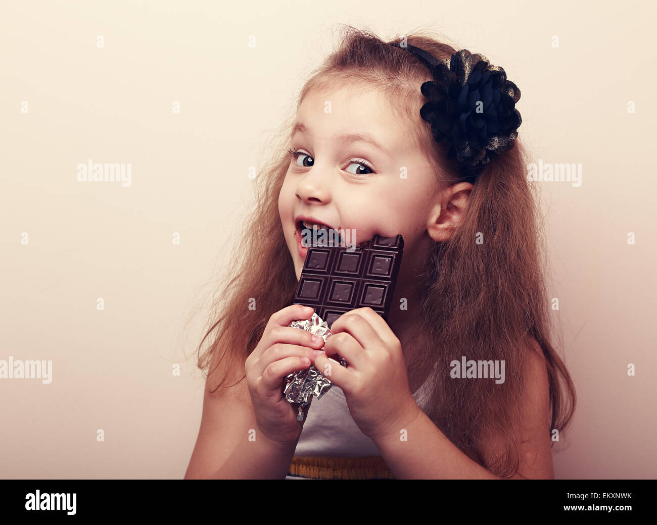 Happy smiling kid girl biting tasty chocolate with empty copy space. Vintage portrait - Stock Image