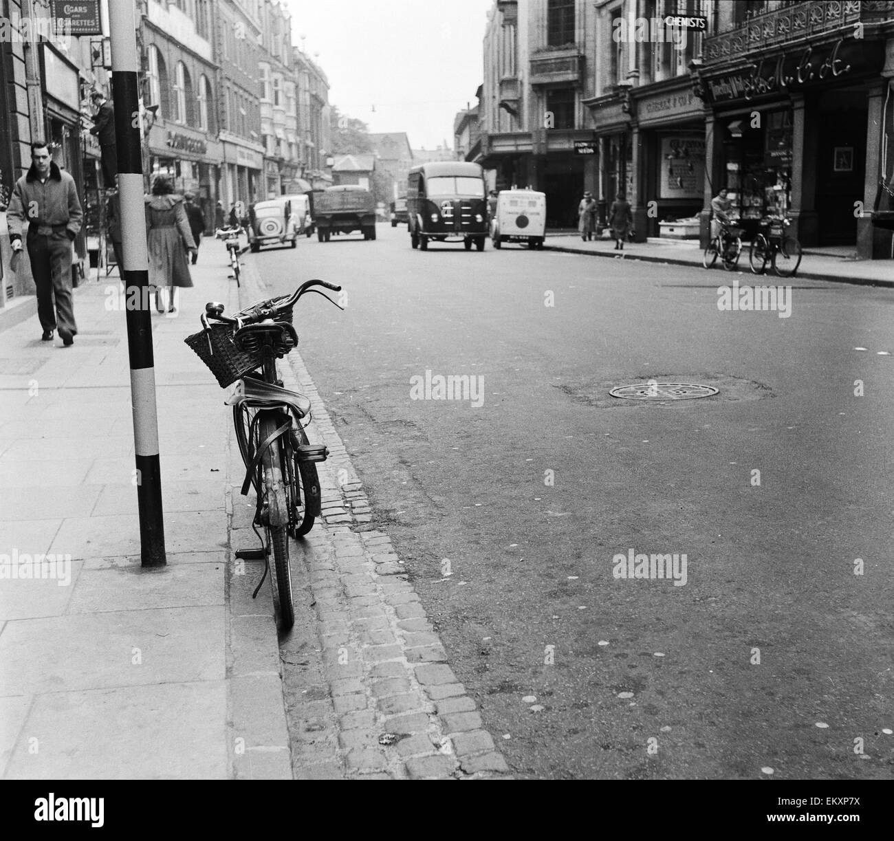 Street scene in Oxford town centre, showing a bicycle parked up against the kerb. 12th October 1952. - Stock Image