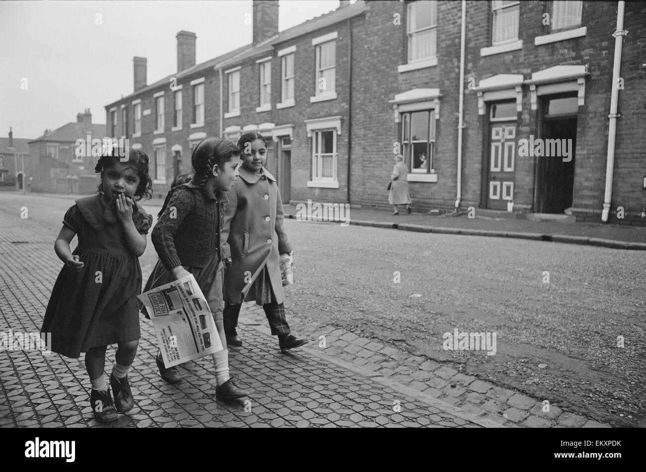 Three asian girls make their way home in Marshall Street Smethwick. 1st December 1964 - Stock Image