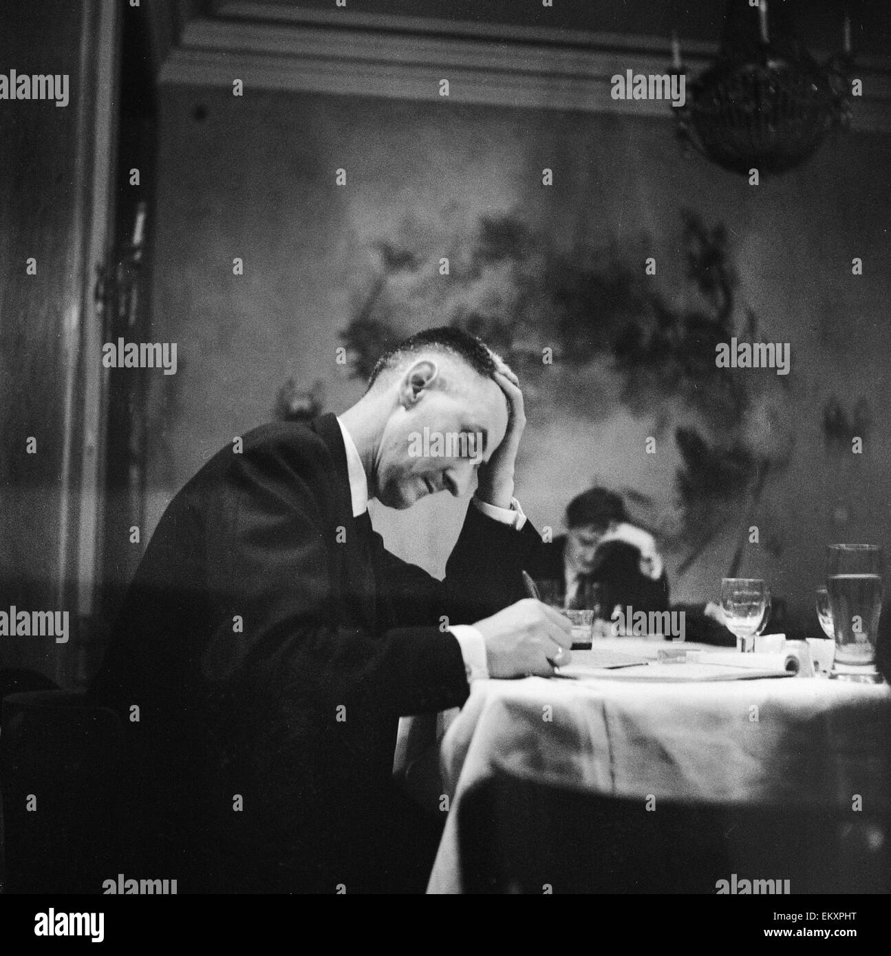 Hungarian Revolution. An unidentified Hungarian man writing at a table in a restaurant. 31st October 1956. - Stock Image