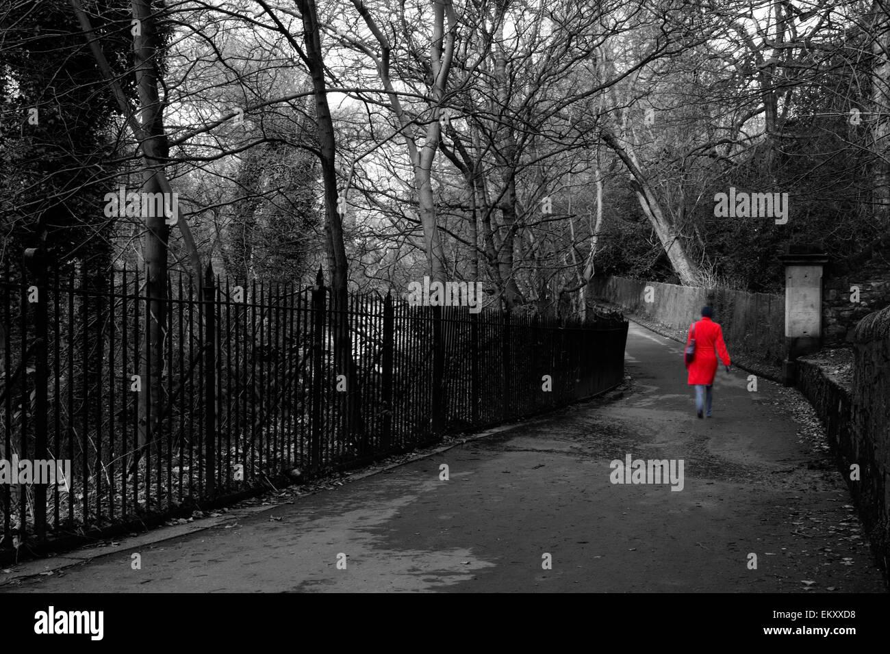 Girl In A Bright Red Coat Walking In a Park of Edinburg, Scotland - Stock Image