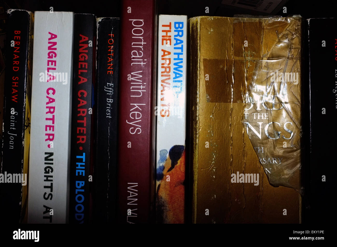 A row of books in varying conditions photographed against a black background. - Stock Image