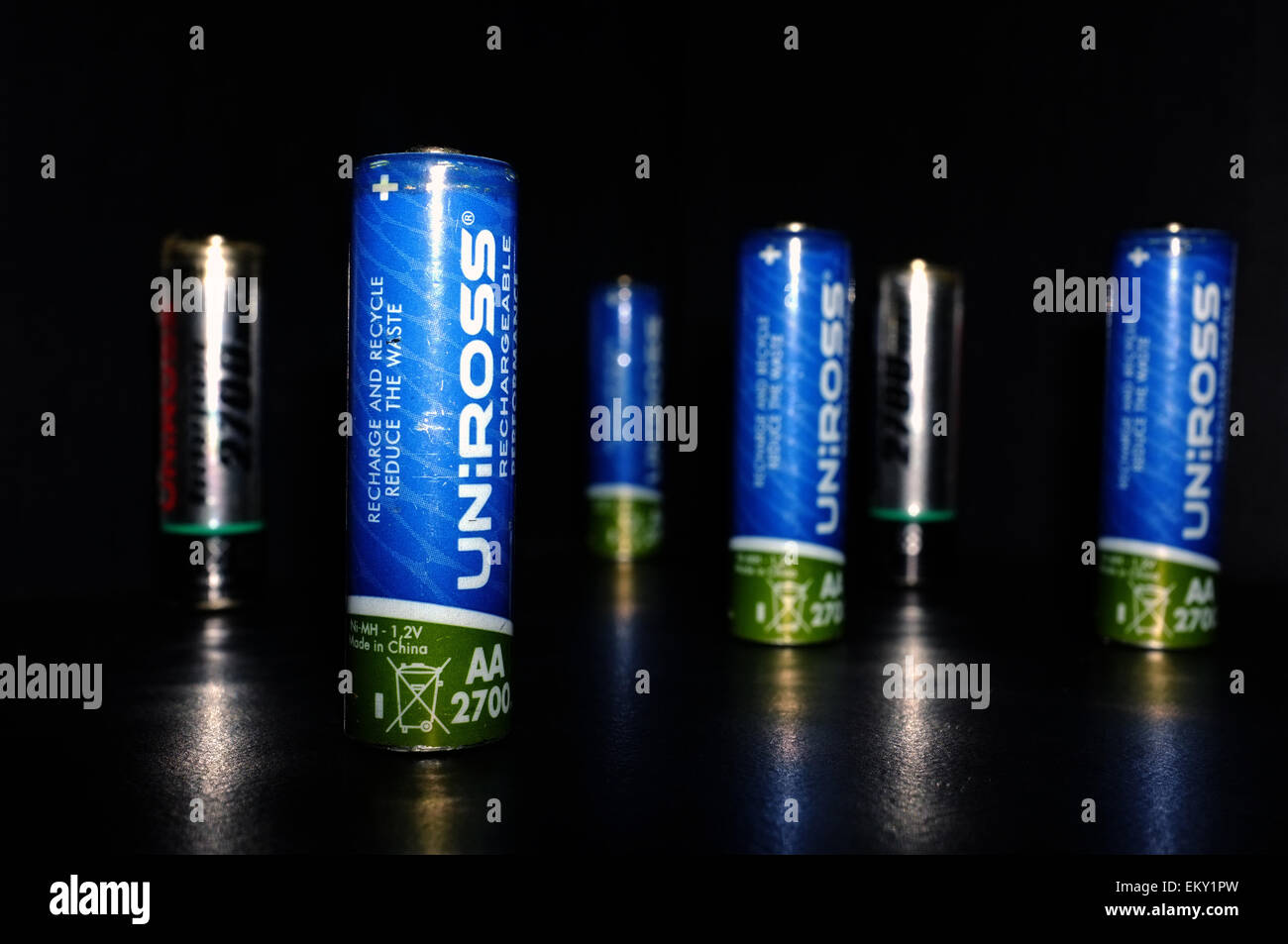 A selection of rechargeable AA batteries photographed against a black background. - Stock Image
