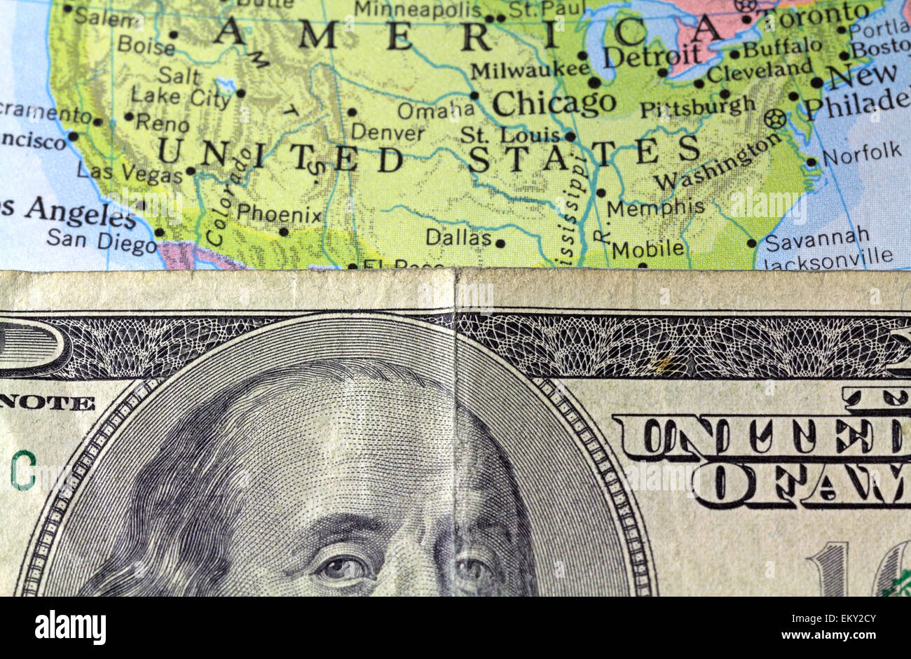 A partial view of Benjamin Franklin on a hundred dollar bill atop an old atlas showing the United States. - Stock Image