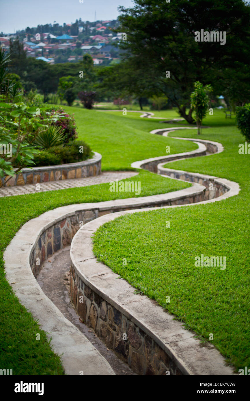 A stone walled path winding through gardens; Kigali, Rwanda - Stock Image