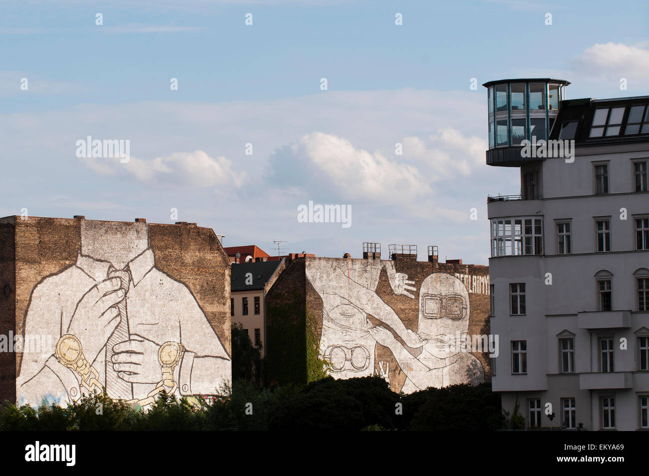 Modern apartment in an old warehouse on the Spree River overlooks street art by BLU. - Stock Image