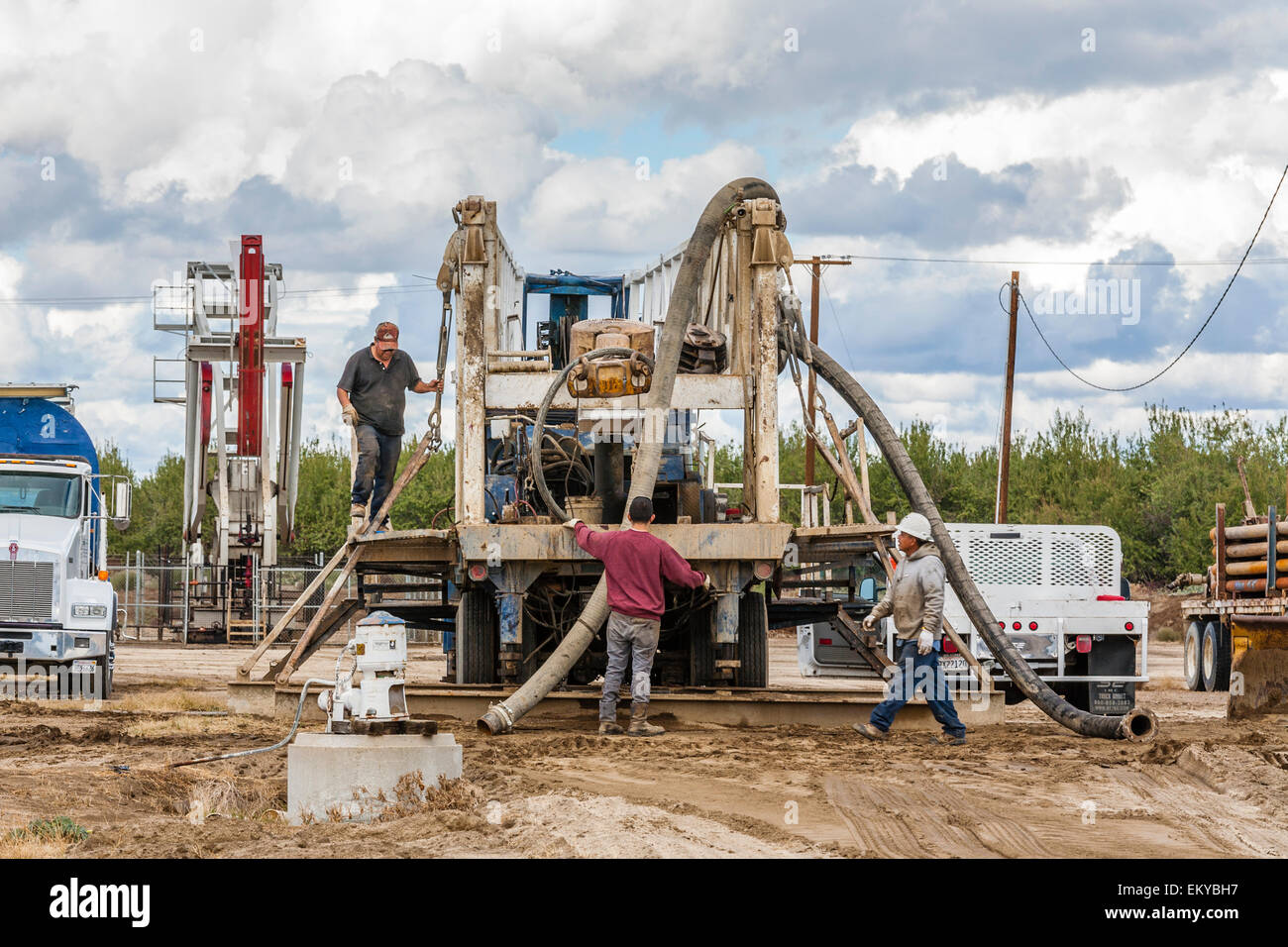 Water well being drilling next to oil well and fracking site in almond orchard. Kern County, California - Stock Image