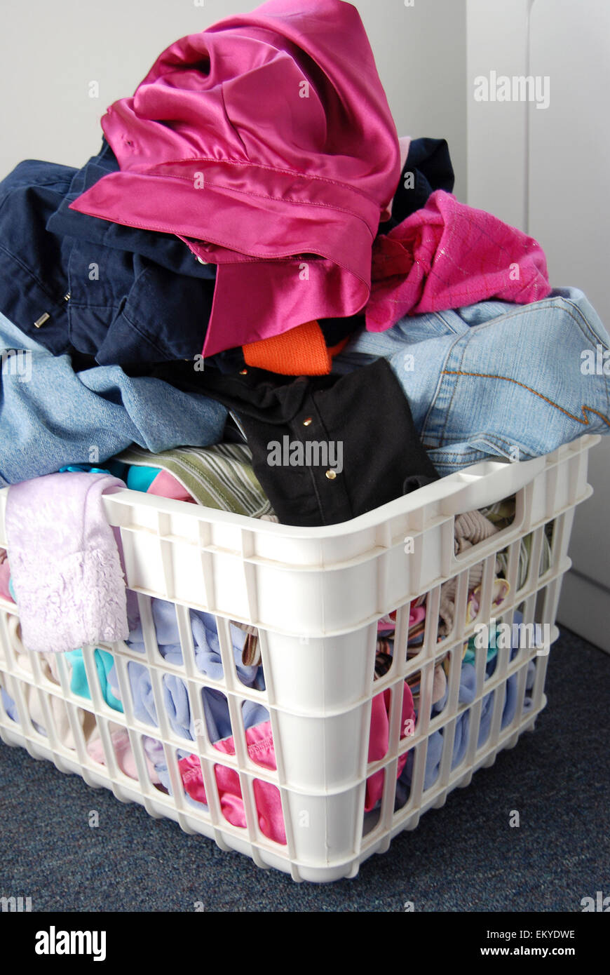 Pile of clean clothes in white laundry basket. - Stock Image