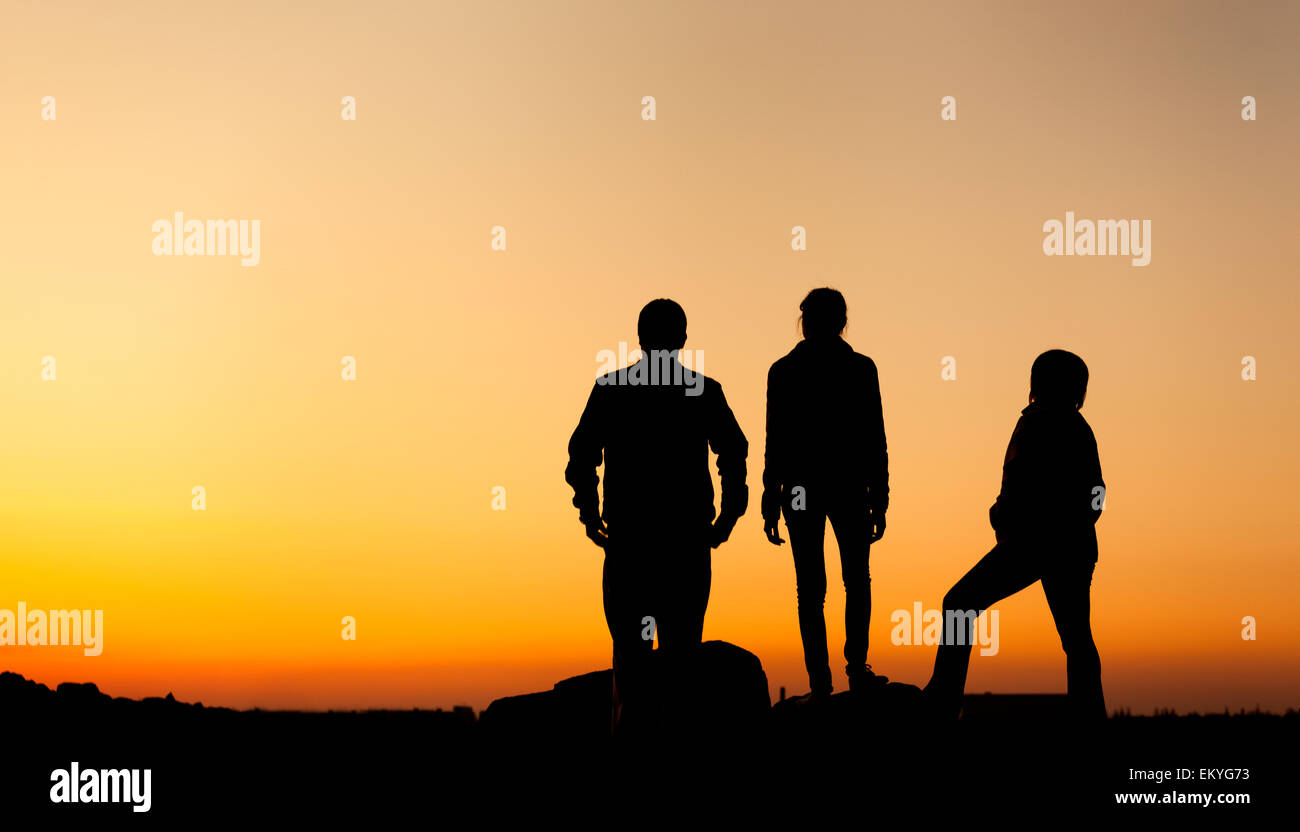 Silhouette of a happy family with arms raised up against beautiful colorful sky. Summer Sunset. Landscape - Stock Image