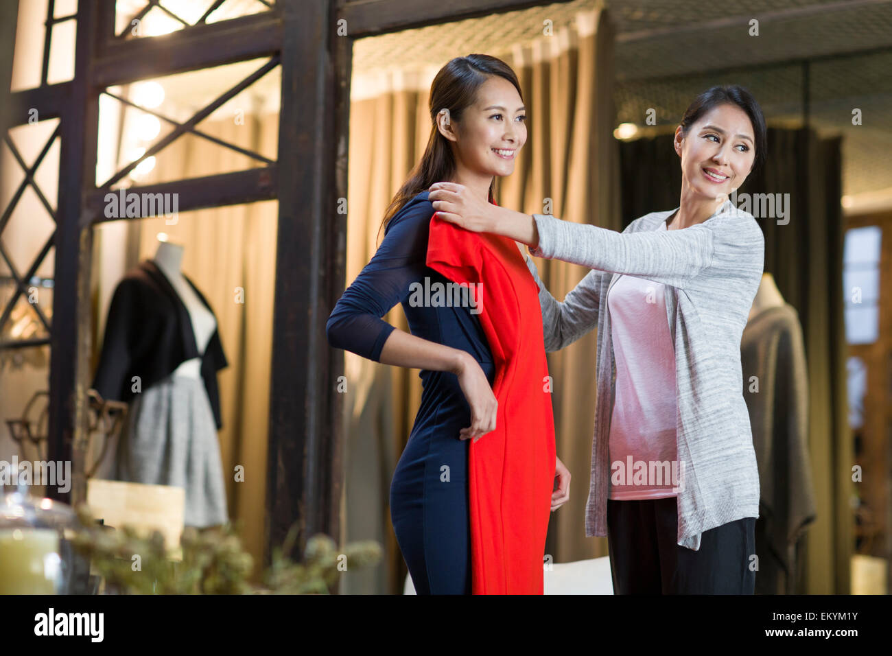 Clothing store owner helping customer with choosing dress - Stock Image