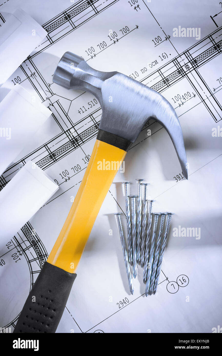 claw hammer and nails with blueprints - Stock Image