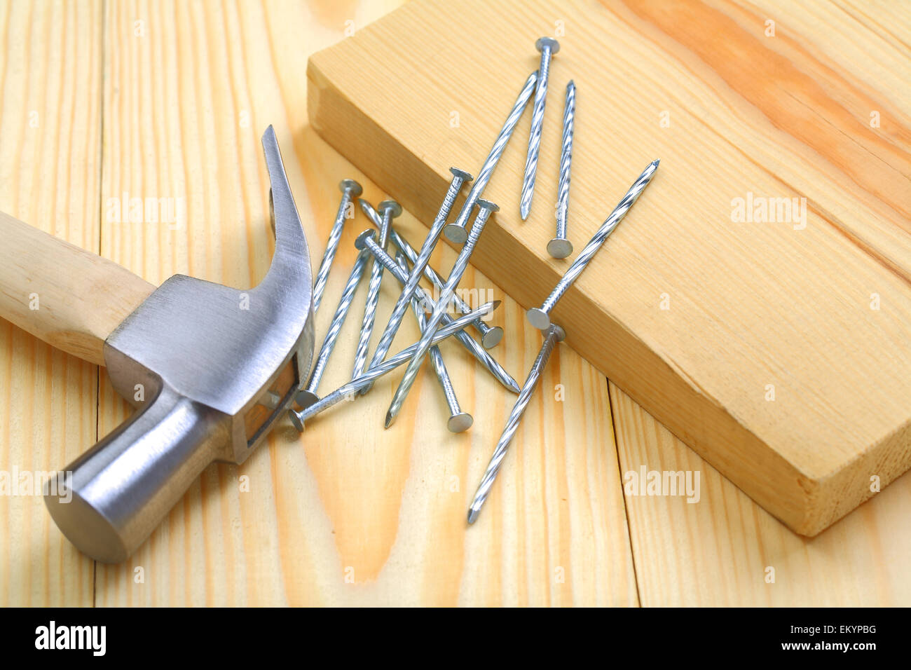 claw hammer with nails and timber on table - Stock Image