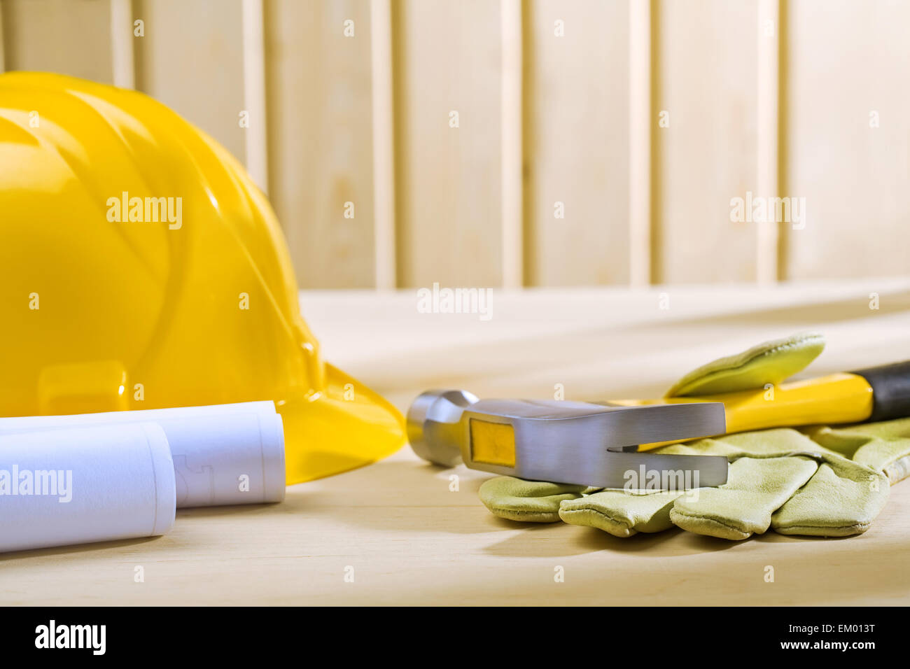 claw hammer on glove and hellmet with blueprints - Stock Image
