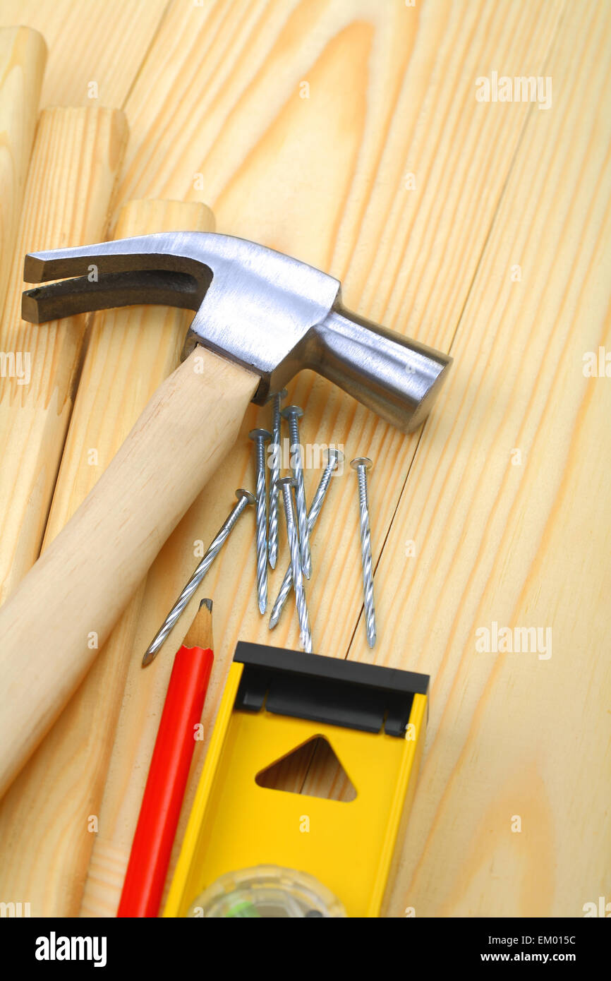 claw hammer with nails and pencil on level - Stock Image