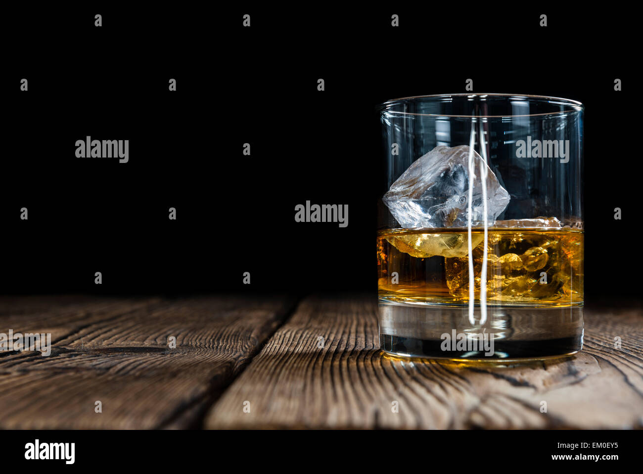 Single Malt Whiskey with Ice Cubes on wooden background - Stock Image