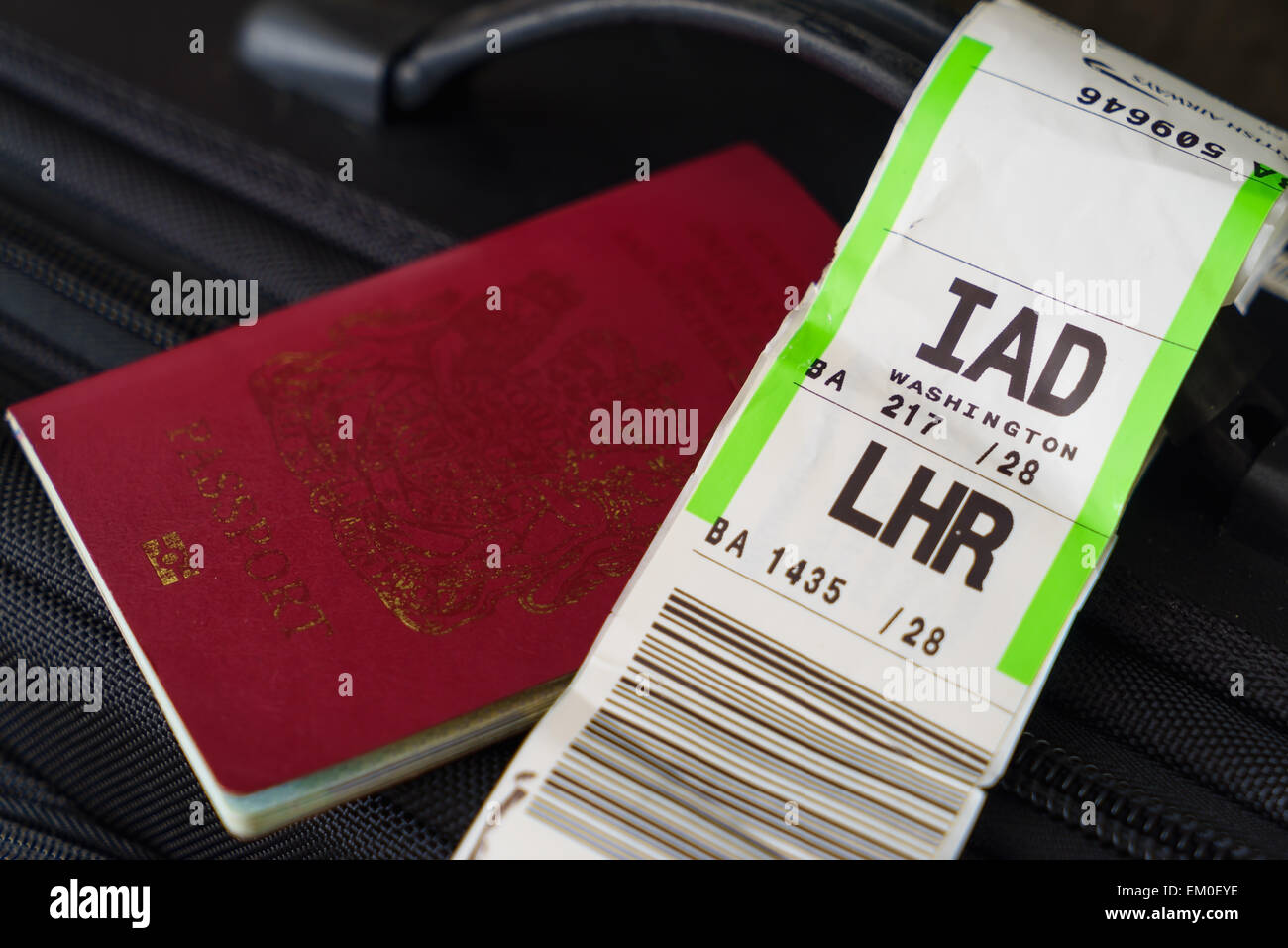 A suitcase with a airline barcode baggage tag from London Heathrow (LHR) to Washington Dulles (IAD), and a red UK - Stock Image