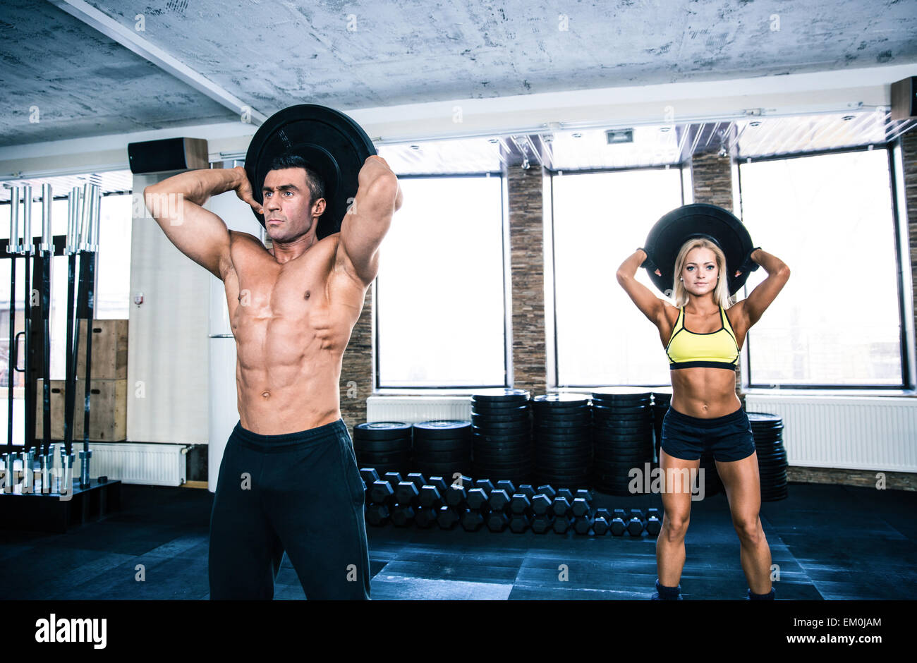 Muscular man and fit woman workout at crossfit gym - Stock Image