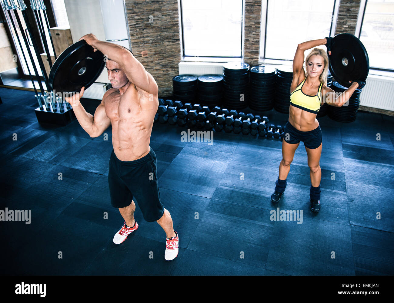 Muscular man and woman workout at crossfit gym - Stock Image