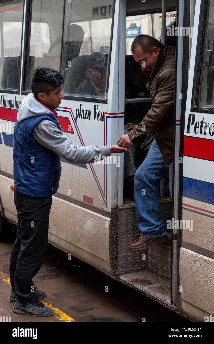Peru, Cusco.  Young Man Collecting Fare from Disembarking Bus Passenger. - Stock Image
