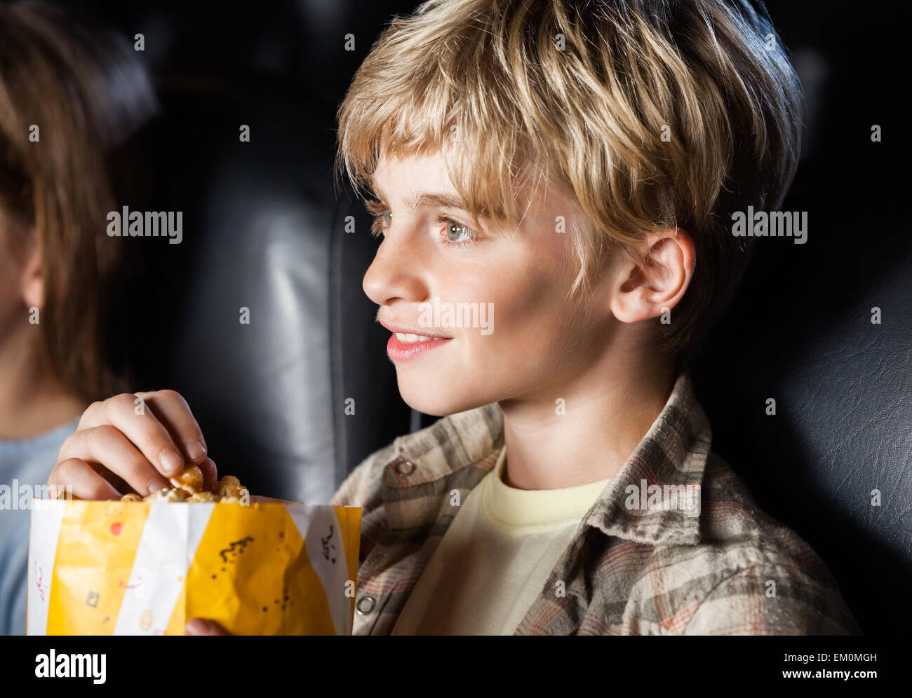 Boy Eating Popcorn While Watching Movie - Stock Image