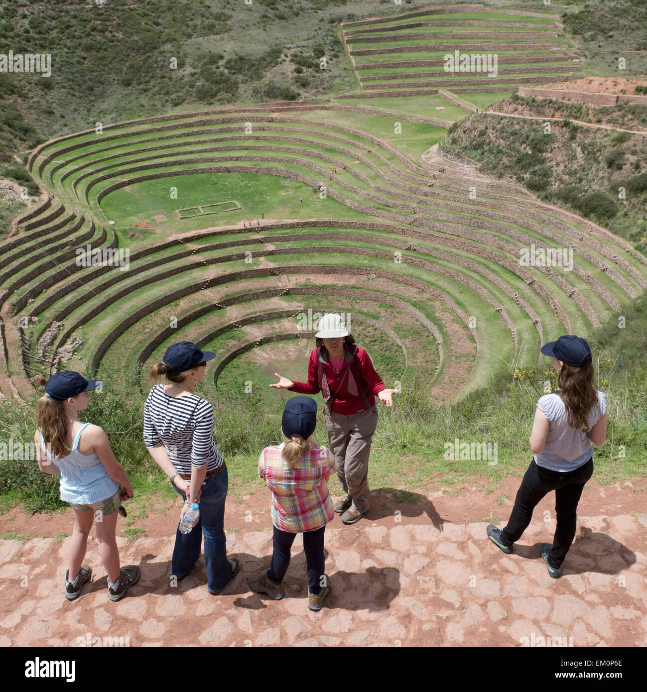 A Group Of Young Women Overlook Concentric Ring Terraces As Part Of The Inca Ruins; Moray Peru - Stock Image