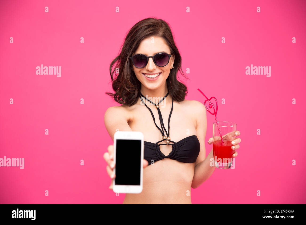 Smiling woman in bikini and glasses holding glass of juice and showing smartphone screen over pink background - Stock Image