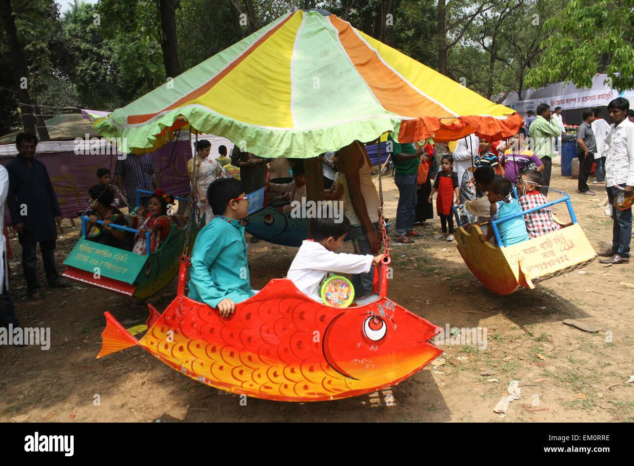 Dhaka, Bangladesh. 14th April, 2015. Bangladeshi children ride a merry-go-round as they celebrate the Bengali New - Stock Image