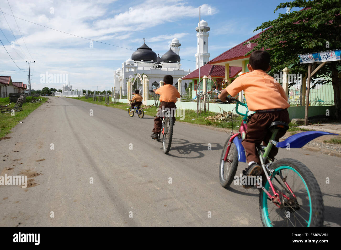 School children cycling along the road in front of a small mosque, near Banda Aceh; Aceh Province, Sumatra, Indonesia Stock Photo
