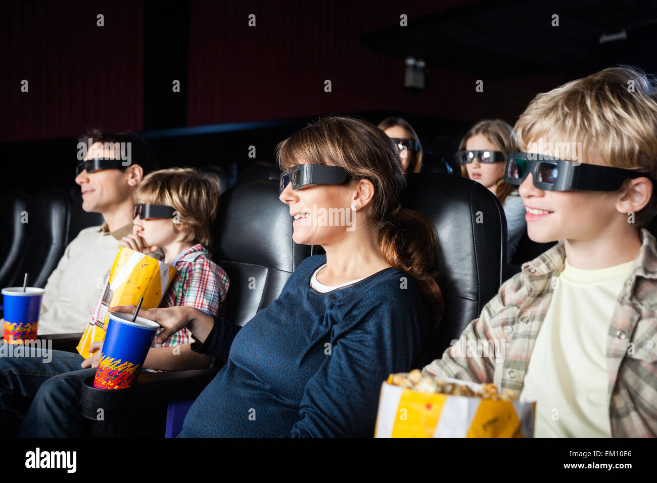 Smiling Families Watching 3D Movie In Theater - Stock Image